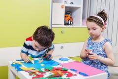 Ребенок дошкольного возраста создает изображение с формами пены Стоковая Фотография