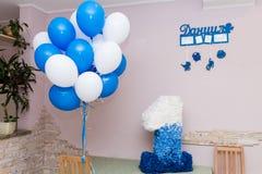 Ребенок одно годовалое Яркая комната ` s детей украшенная с воздушными шарами, игрушки и большое количество одно покрашенной бума Стоковая Фотография RF