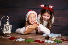 Ребенок пишет письмо к Санта Клаусу Смешные девушки в шляпе Санты пишут письмо к Санте Стоковое Фото