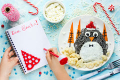 Ребенок пишет письмо для santa, списка целей к рождеству на таблице w Стоковые Изображения