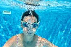 Ребенок плавает под водой в бассейне, счастливых активных пикированиях девушки подростка и имеет потеху под водой, фитнесом ребен стоковая фотография