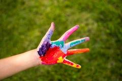 Ребенок покрашенный рукой на зеленой предпосылке стоковое изображение rf