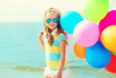 Ребенок портрета счастливый на пляже лета с красочными воздушными шарами стоковые фотографии rf