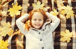 Ребенок портрета счастливый усмехаясь лежа имеющ потеху с желтыми листьями клена в взгляд сверху дня осени Стоковое Изображение RF