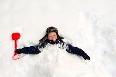 Ребенок похоронил с лопаткоулавливателем детей вокруг шеи в снеге стоковая фотография rf