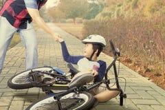 Ребенок получает аварию с велосипедом и, который помог папа стоковые изображения