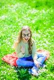 Ребенок представляя с eyeglasses картона для фотосессии на луге Девушка на жизнерадостной стороне тратит отдых outdoors франтовск стоковые фото
