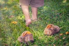 Ребенок принимает ботинки Нога ребенка учит идти на траву Стоковые Фотографии RF