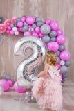 Ребенок принцессы празднуя событие в жизни нося золотую крону и розовое воздушное платье Милая девушка представляя во всходе студ стоковые фото