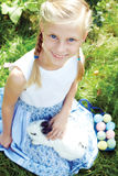 Ребенок при белый зайчик ища для красочных яичек на луге Стоковые Изображения