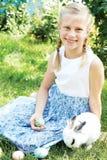 Ребенок при белый зайчик ища для красочных яичек на луге Стоковые Изображения RF