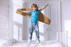 Ребенок при крыла картона скача на кровать стоковое фото