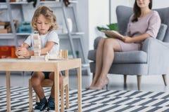 Ребенок при синдром Asperger играя с деревянными блоками во время терапевтической встречи с терапевтом в центре наличия семьи стоковые фото