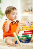 Ребенок при eyeglasses играя абакус Стоковая Фотография RF