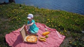 Ребенок раскрывает картонную коробку с пиццей на береге моря видеоматериал