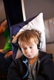 Ребенок расслабляющий и смотрящ фильм в воздушном судне в деле Стоковые Фотографии RF
