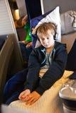 Ребенок расслабляющий и смотрящ фильм в воздушном судне в деле Стоковые Фото