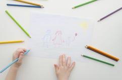 Ребенок рисует его семью с карандашами Чертеж и покрашенные карандаши ребенка Чертеж семьи на белой бумаге Взгляд сверху стоковые изображения