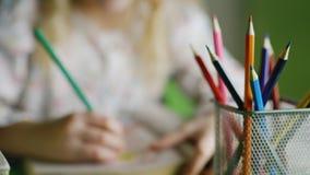 Ребенок рисует, малая глубина поля На переднем плане, ваза с покрашенными карандашами, ее руки ` s детей рисует видеоматериал