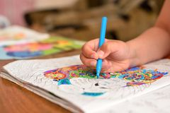 Ребенок рисует ручку войлок-подсказки в его альбоме стоковая фотография rf