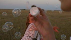 Ребенок, сестры и игра матери совместно Счастливая мать играя с детьми дуя пузыри мыла дети улавливают пузыри видеоматериал