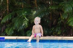 Ребенок сидит на краю бассейна Маленький младенец отдыхает около бассейна стоковая фотография