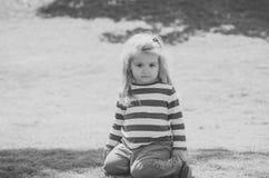 Ребенок сидит на лужайке зеленой травы Стоковое Фото