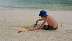 Ребенок сидит на пляже около воды и выкапывает отверстие с лопаткоулавливателем видеоматериал