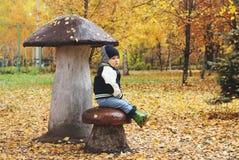 Ребенок сидя большие листья желтого цвета осени гриба Стоковое Фото