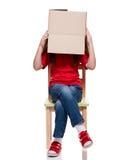 Ребенок сидя на стуле с большой коробкой покрыл головку Стоковые Фото