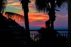Ребенок силуэта на заходе солнца Мальчик стоит на балконе между заходом солнца и ладонью Красного Моря Драматический заход солнца Стоковые Изображения