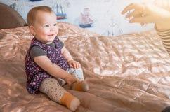 Ребенок сидит на кровати и усмехаться Стоковые Изображения