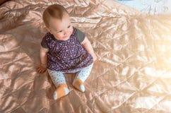 Ребенок сидит на кровати и усмехаться Стоковая Фотография