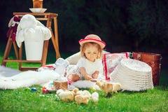 Ребенок сидит на луге вокруг украшения пасхи Стоковое фото RF