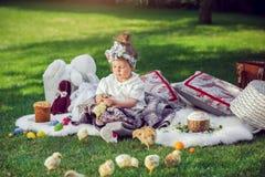 Ребенок сидит на луге вокруг украшения пасхи Стоковые Изображения RF