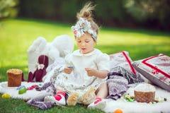 Ребенок сидит на луге вокруг украшения пасхи Стоковые Фото