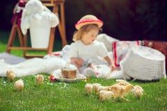 Ребенок сидит на луге вокруг украшения пасхи Стоковое Изображение RF