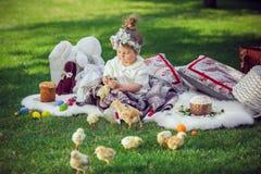 Ребенок сидит на луге вокруг украшения пасхи Стоковое Изображение