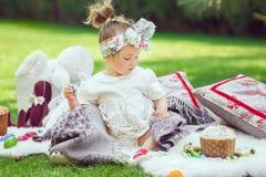 Ребенок сидит на луге вокруг украшения пасхи Стоковая Фотография RF