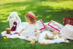 Ребенок сидит на луге вокруг украшения пасхи Стоковые Фотографии RF