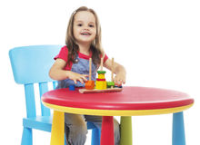 Ребенок сидя на таблице и играть Стоковая Фотография
