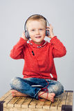 Ребенок сидя с пересеченными ногами и слушая к музыке Стоковые Изображения RF