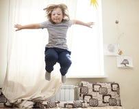 Ребенок скача на кровать в спальне стоковые изображения rf