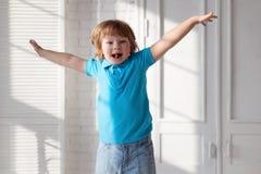 Ребенок скача на кровать в спальне стоковое фото rf