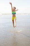 Ребенок скача на пляж Стоковое Изображение