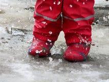Ребенок скача для лужиц на дорогах таяет в конце зимы Стоковые Фото