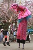 Ребенок скачет для того чтобы дать высоко--5 к ходоку ходулей стоковая фотография rf
