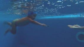 Ребенок скачет к бассейну и заплыванию под водой к его маме видеоматериал
