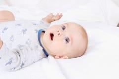 Ребенок смешного младенца младенческий при голубые глазы лежа на кровати Стоковые Изображения
