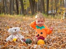 Ребенок смеясь и играя в осени стоковое фото